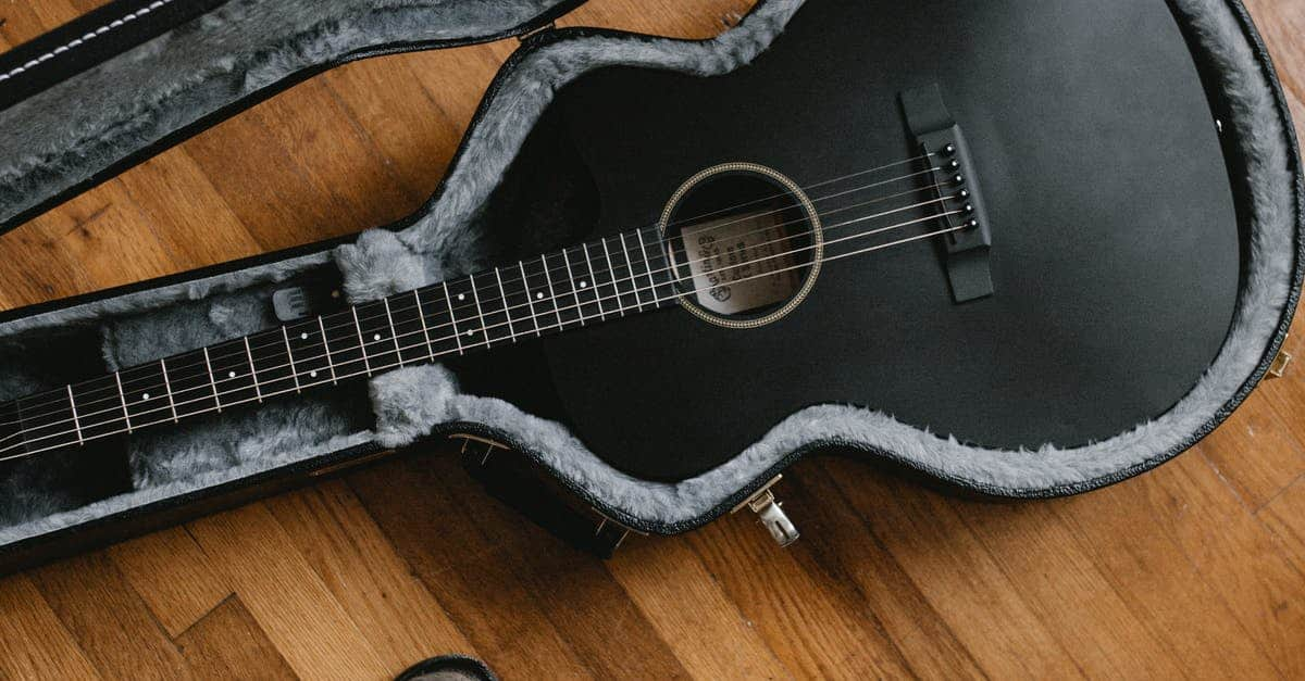 A brown guitar on a wooden floor
