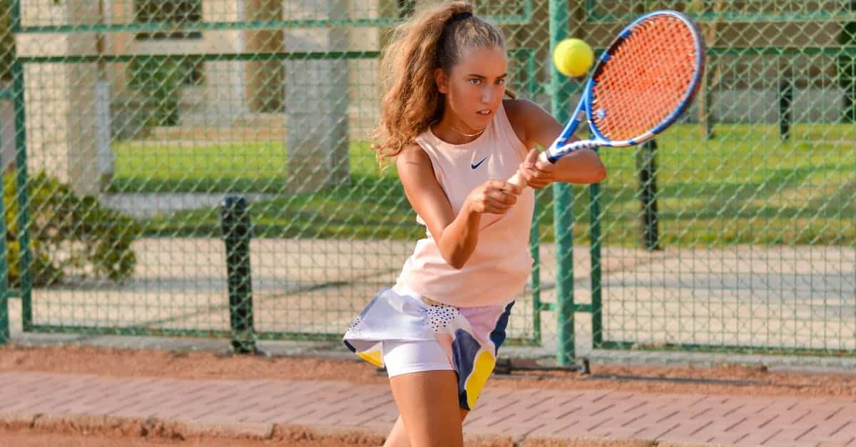 A girl is swinging a racket at a ball