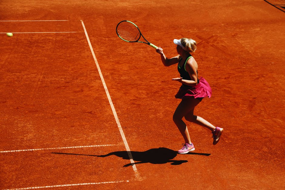 A person with a racket on a tennis court holding a racquet