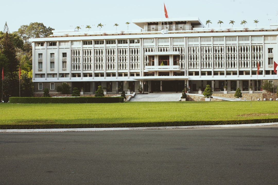 A large building by a road with Independence Palace in the background