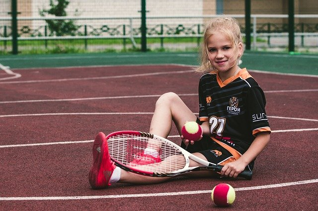 A little girl holding a racket on a court